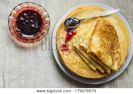 Pile of folded golden crepes on white plate spilled black currant jam in crystal rosette spoon linen cloth top view