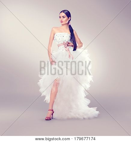 Beauty fashion Young brunette model Bride in wedding dress with long train posing in studio. Wedding Dress salon. Beautiful fiancee in elegant white wedding dress, perfect makeup and hairstyle