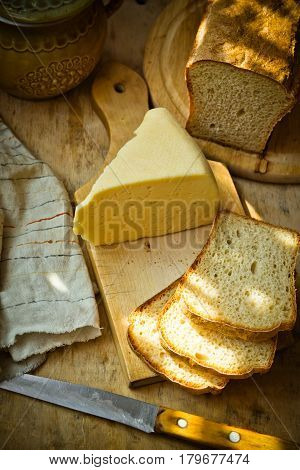 Chunk of cheese loaf of sourdough bread on wood cutting board linen napkin rustic kitchen interior sunlight flecks cozy atmosphere