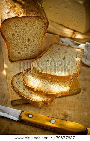 Loaf of sourdough whole wheat bread cut into slices golden crust chunk of cheese linen towel wood kitchen table sunlight spots top view