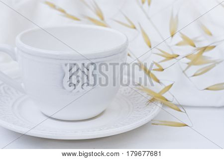 White elegant tea cup with saucer dry plants wild oats white cotton fabric styled image for social image blogging marketing