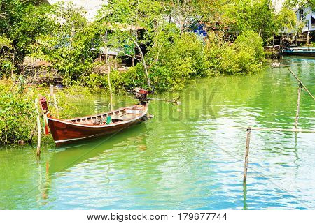 Long tail boat with fishing village In Sikao Thailand.