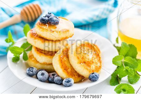 Cottage cheese pancakes with honey and blueberry on white background breakfast or lunch