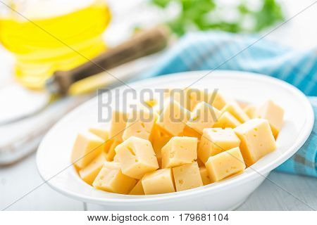 Cheese slices on plate on white background