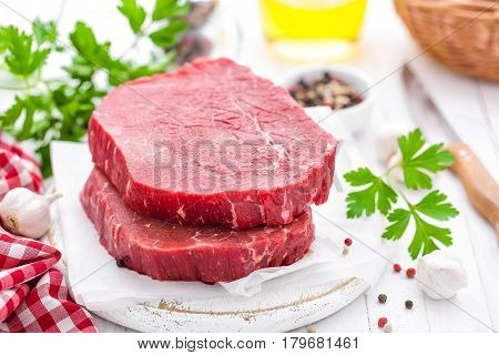 Raw uncooked beef meat steaks on white wooden background
