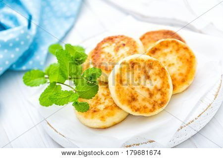 Cottage cheese fritters on white wooden background closeup