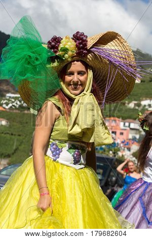 ESTREITO DE CAMARA DE LOBOS PORTUGAL - SEPTEMBER 10 2016: Women wearing in colorful costume at Madeira Wine Festival in Estreito de Camara de Lobos Madeira Portugal. The Madeira Wine Festival honors the grape harvest with a celebration of traditional loca