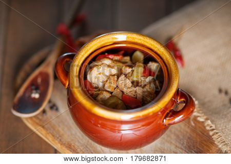 Beef meat stewed with vegetables in ceramic pot