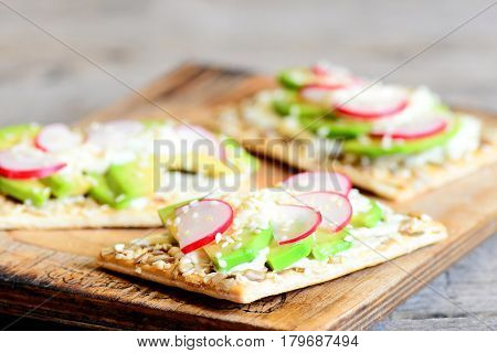 Healthy and quick veggie cracker with sauce and vegetables. Sliced avocado and radishes on crispy cracker with seeds on wooden board. Closeup