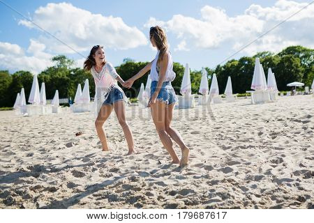 Happy Pretty Woman Holding Her Friend By Hand Leading Her
