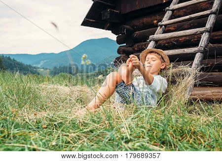 Boy rest in green grass under hayloft in summer afternoon