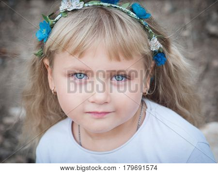 Blonde little girl is smiling at the camera.