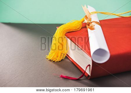 close up of book diploma and tassel of graduation cap with copy space education concept