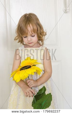 little cute girl in yellow dress with a sunflower watches on the flower