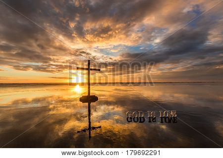 Cross on a beach at Sunset with a wonderful reflection and the word God is Love.
