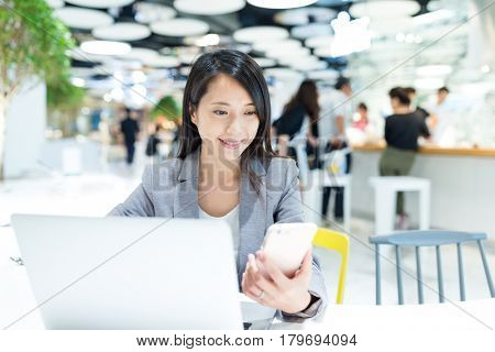 Business woman working on laptop computer and cellphone