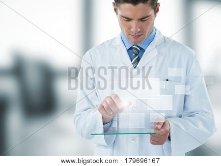 Digital composite of Man in lab coat looking down at glass device and square interface against blurry window