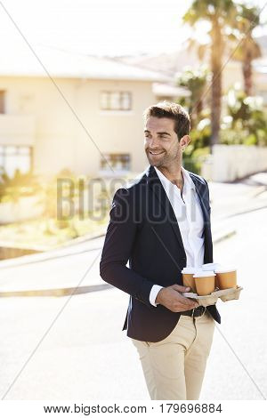 Smiling man with coffee in sunlit street smiling