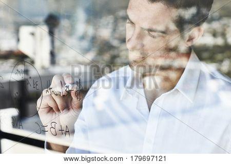 Businessman drawing statistics and ideas on window