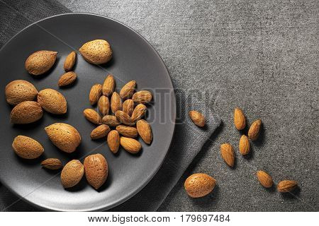 Almonds nuts in their skins and peeled on gray background