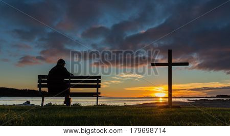 A man on a seat next to a cross watching the sunset at Foxton Beach river.