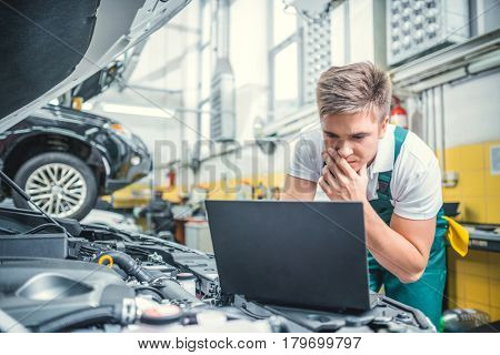 Young man with computer in service