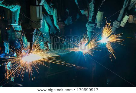 robots is welding movement in a car factory