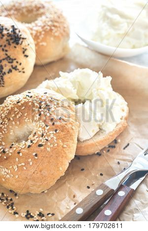 Bagel with cream cheese on the baking paper