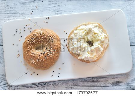 Bagel with cream cheese on the white plate