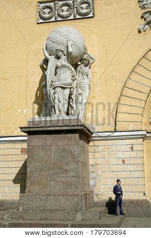 Saint-Petersburg, Russia - May 14, 2006: Sentry stands near Statues of nymphs carrying the globe on the facade of the Main Admiralty