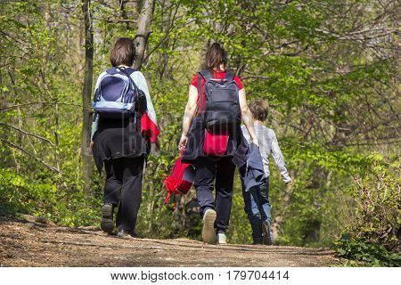 Two women and child going for a walk in a forest