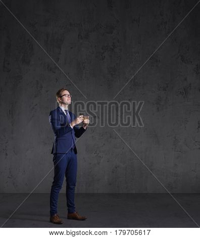 Businessman standing with smartphone on a dark background. Business, career, job concept.