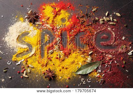 Word Spice drawing on various spices on stone table. Top view