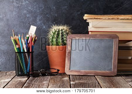 Supplies, cactus and chalk board for your text. Back to school concept with copy space