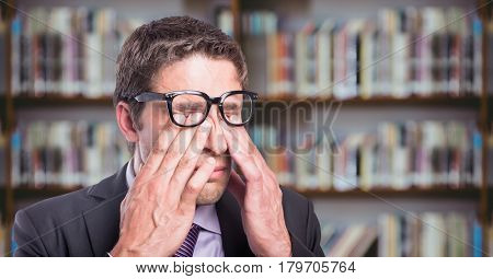 Digital composite of Business man rubbing eyes against blurry bookshelf