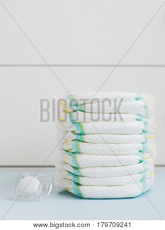 A stack of diapers against a white wardrobe