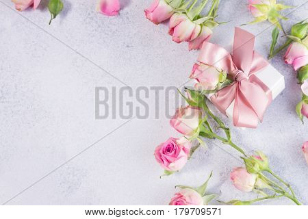Gift box with pink satin bow and rose flowers with copy space