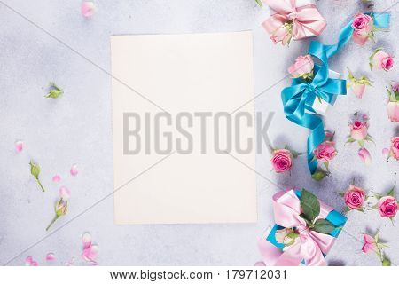 Gift boxes with pink satin bows and rose flowers, copy space on vintage paper