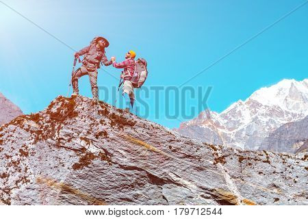 Happy People shaking Hands on top of Rock in Mountain Scenery during challenging Hike in Nepal Himalayas