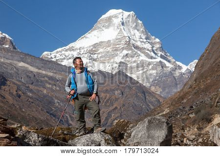 Mature high Altitude Himalaya Nepalese Mountain Guide staying on Rock with Backpack and looking Up