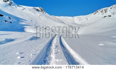Deep ski trails in fresh snow against the blue sky and snowy mountains. Ski trip. Subpolar Urals, Russia.