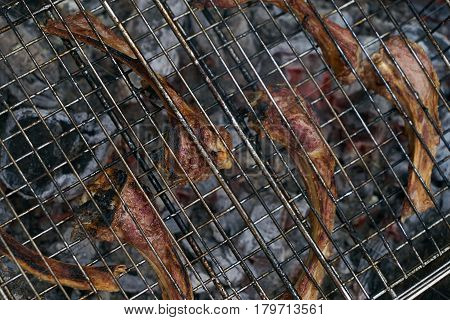 Close up of Cooking delicious barbecued lamb ribs . Lamb ribs at outdoors grill. Summer Weekend and party concept.