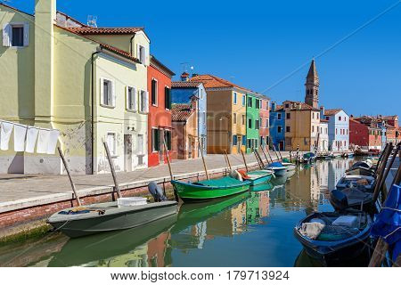 Colorful houses along small canal with boats in Burano, Italy.