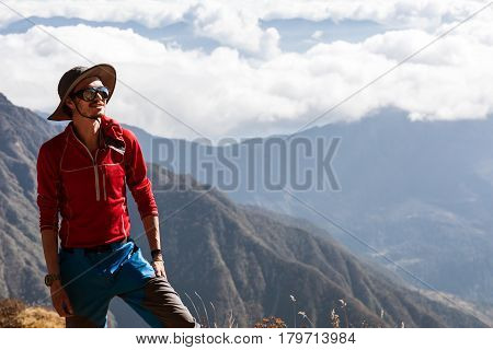 Portrait of young smiling Hiker in fedora Hat with Mountains and Cloud Cover on Background