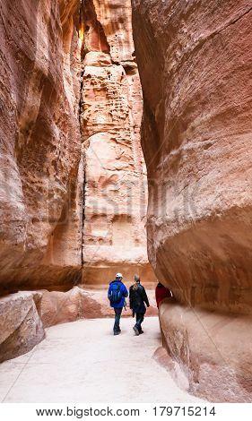 Tourists Walk In Narrow Siq Passage To Petra Town
