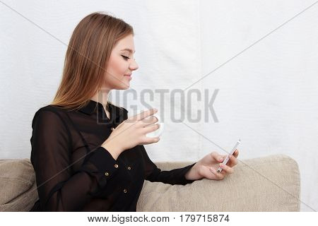 Young beautiful woman using her smartphone on the couch at home in the living room. Cute blond girl chating with friend or shopping online