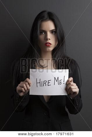 """Sexy young woman holding a paper with the text message """"Hire me""""."""
