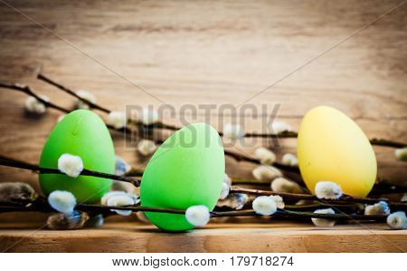 easter eggs and pussy willow on rustic wooden background