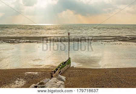 Shingle and sand beach at low tide. Ferring near Worthing in West Sussex England. With groyne sea defences.