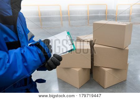 Closeup shooting hand of QC. worker with clipboard checking to goods package boxes in the cold room warehouse. Food cold storage concept